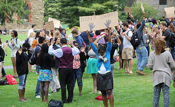 Colgate community members collectively put their hands up in a demonstration of their solidarity with Ferguson. Photo by Salote Tenisi '15