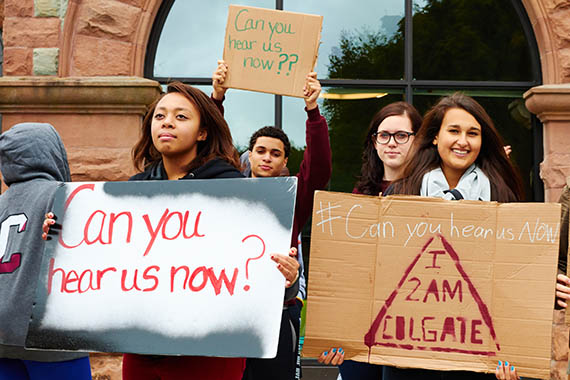 Students use signs to ask can you hear us now during demonstration outside James B. Colgate Hall