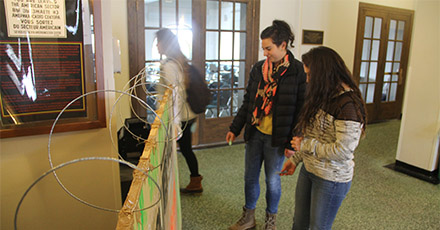 Two students examine a commemorative Berlin Wall in Lawrence Hall at Colgate University