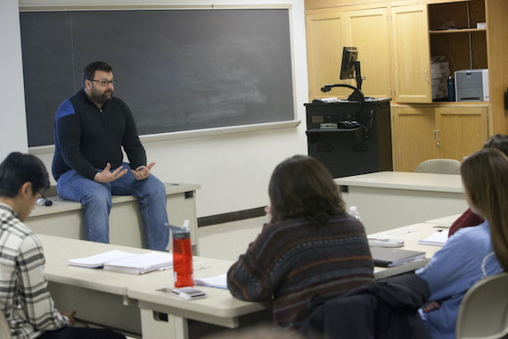 Jason Keith sits on a table in a classroom in Olin Hall.