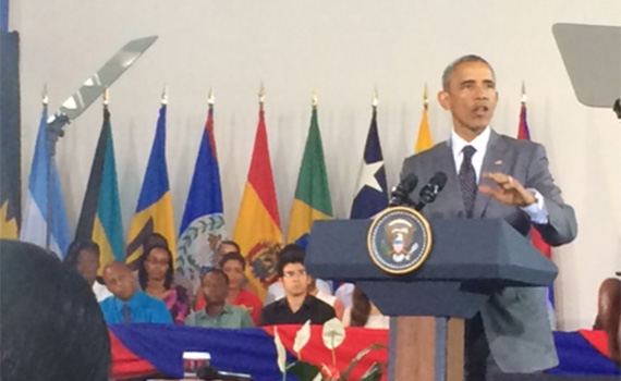 President Obama at a podium addressing a town hall event in Jamaica.