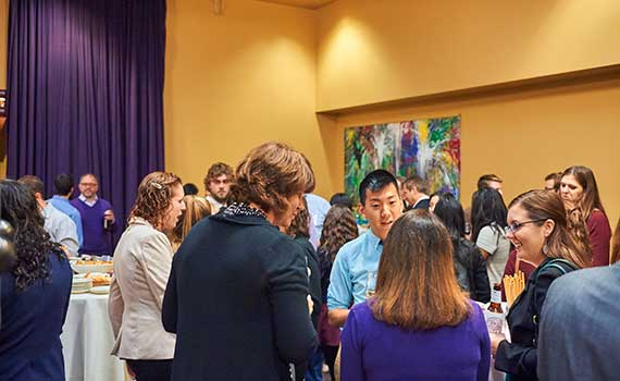 Students and alumni stand together at networking event