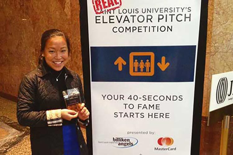 "Miranda Scott '18 stands by a poster at the ""Real"" Elevator Pitch competition in St. Louis, Mo."