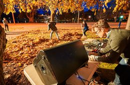 Chris Kallmyer adjusts sound levels on his computer while students rake leaves