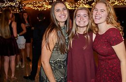 Three students stand together smiling in the Hall of Presidents during the Colgate Lymphoma Gala