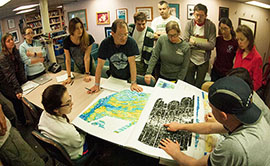 Scientists gather around a table full of maps