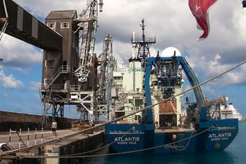 Research vessel Atlantis sits beside a dock.