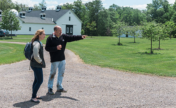Grace Thomas '17 stands with Bob Sutherland outside of a barn at Mohican Farms