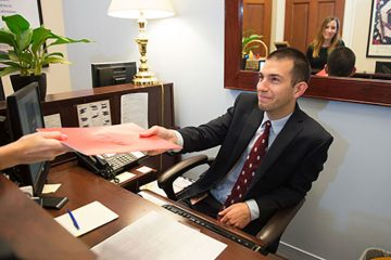 Kevin Costello '16 hands a file across a desk in the office of Congressman Richard Hanna