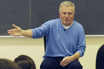 Duncan Niederauer '81 with his hand extended while addressing students