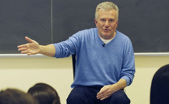 Duncan Niederauer '81, former CEO of the New York Stock Exchange sits on a desk and talks to students in a classroom