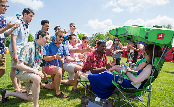 A cappella singers serenading two women seated in lawn chairs