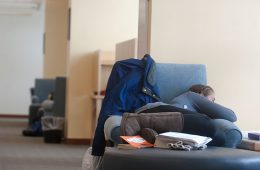 Student sleeping in a chair surrounded by books.