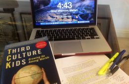 Third Culture Kids book, laptop, and paper with highlighter