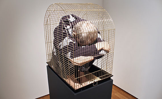 Marko Mäetamm, Self-Portrait in the Cage, 2015, cast plastic figure, hair, clothes, and birdcage; 33 1/8 x 17 1/2 x 27 3/8 in. (84.1 x 44.5 x 69.5 cm). Image courtesy of Marko Mäetamm and Temnikova & Kasela Gallery.