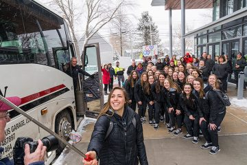 Player Olivia Zafuto uses a selfie stick to take a team picture in front of the team bus
