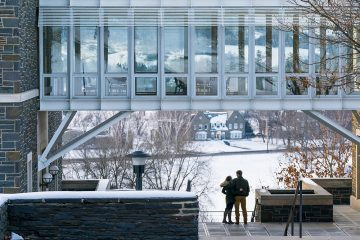 Couple looks out over snowy campus