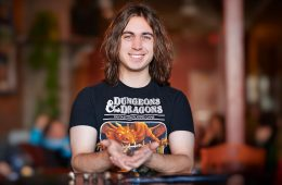 Ian Dwyer '14 in a Dungeons and Dragons t-shirt holding playing dice.