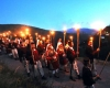 Men and women march with torches on a hillside at dusk