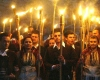 Men and women march with torches at night