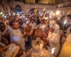 Men and women hold small torches at night while dressed in white