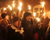 Smiling men and women walk in winter attire at night holding torches