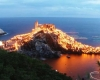 Torches cover a rocky peninsula surrounding a castle at dusk