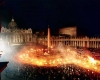 Torches process in the dark outside St. Peter's Basilica in the Vatican