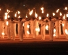 Men dressed in white stand in lines holding torches out to their sides