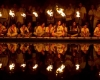 Male and female scouts seated along a body of water behind a row of lanterns
