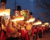 Men in red gowns carrying torches alongside a festive float
