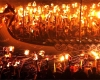 People hold torches on either side of a long ship with a dragon's head