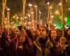 A crowd of men and women holds torches at night