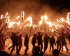A crowd forms a circle and thrusts torches inward