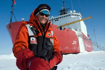 Elizabeth Arnold '82 standing on ice in front of a ship
