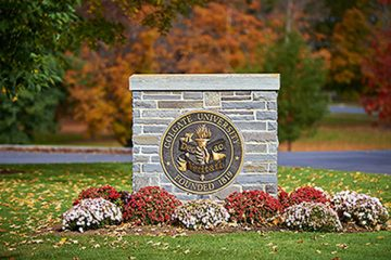 A stone marker on campus featuring the Colgate seal
