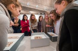 Students examine Egyptian artifacts as part of class.