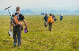 Researchers with packs walk across an open field.