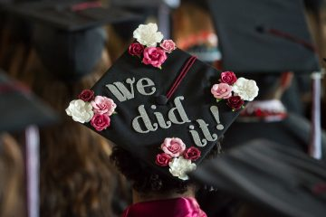 "back of graduation cap reading ""we did it!"""