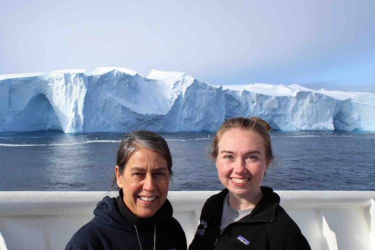 Meghan Duffy '18 and Professor Amy Leventer stand on ship's deck in front of iceberg