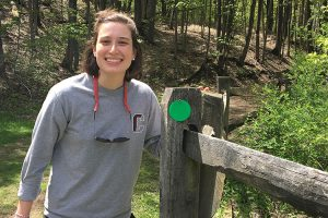 Jenna Lilly stands on the cross country course next to a new trail marker