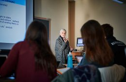 Colgate Professor Ellen Kraly lectures at the front of a classroom