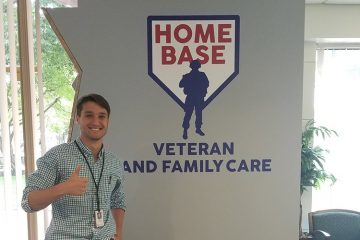 Peter Tappenden '18 gives the thumbs up in front of the Home Base sign