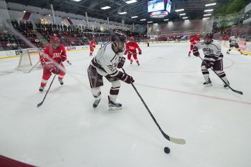 Colgate men's hockey player reaches out for puck in game against Cornell