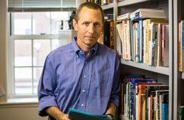 Man standing near book shelf