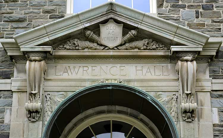 Entrance to Lawrence Hall with a carving of two torches flanking a shield reading Deo ac veritati