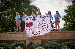 Students stand on wall beside Oak Drive welcoming members of the Class of 2021 to campus