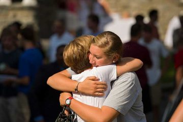 Mother and daughter hug at arrival day social