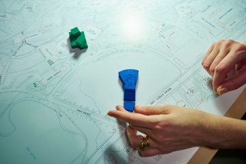 Hand holds model of building on campus map