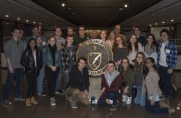 Advent of the Atomic Bomb students in group portrait in front of the seal of the National Nuclear Security Administration